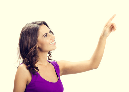 view woman: Profile view of happy smiling beautiful young woman in casual smart lilac clothing, showing copyspace, visual imaginary or something, or pressing virual button
