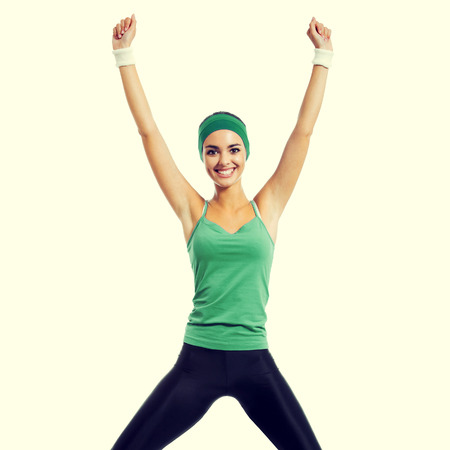 cheerful smiling jumping brunette woman in green fitness wear