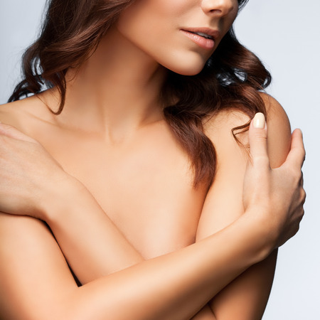 femme se deshabille: belle jeune femme avec les bras crois�s sur sa poitrine, les �paules nues et les yeux ferm�s, sur fond gris clair, composition carr� Banque d'images