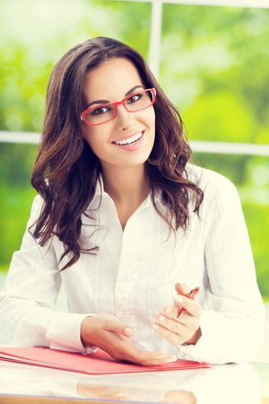 person writing: Portrait of young happy lovely brunette businesswoman at workplace