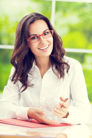 persona escribiendo: Retrato de joven feliz hermosa morena de negocios en el lugar de trabajo Foto de archivo