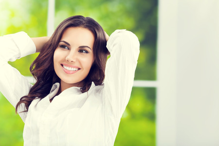 raised arms: Young happy smiling attractive brunette businesswoman with raised arms, at office Stock Photo