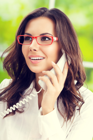 one person: Portrait of attractive brunette businesswoman or support phone worker, at office