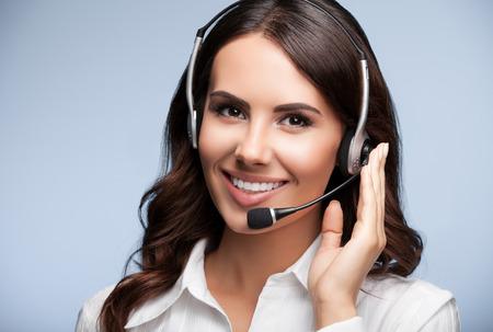 Retrato de feliz sonriente atención al cliente de la operadora de telefonía en el auricular, contra el fondo gris. Consultoría y servicio de asistencia call center. Foto de archivo