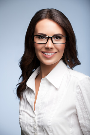 Portrait of smiling young cheerful brunette businesswoman in glasses, over grey background