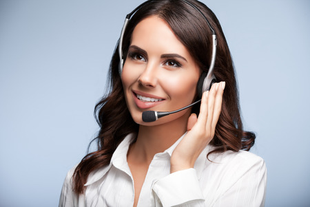 helpline: cheerful customer support female phone operator in headset, against grey background. Consulting and assistance service call center.