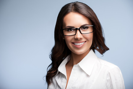 business attire teacher: Happy smiling young cheerful brunette businesswoman in glasses, over grey background Stock Photo