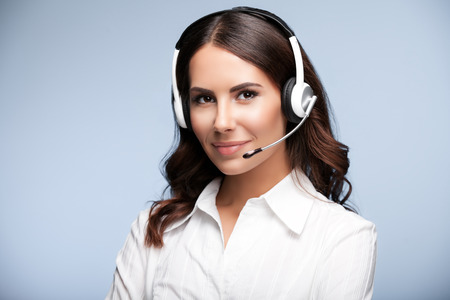 Portrait of smiling customer support female phone worker, against grey background. Consulting and assistance service call center.