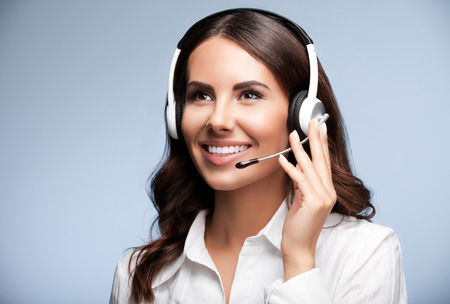 sales agent: Portrait of cheerful customer support female phone worker, looking up, against grey background. Consulting and assistance service call center. Stock Photo