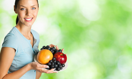 part of me: Joven mujer feliz sonriendo con plato de frutas, al aire libre. Para proporcionar la máxima calidad, he hecho esta imagen, por la combinación de dos fotos. Puede utilizar parte derecha lema, texto grande o banner.