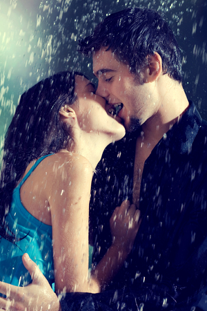 Young couple hugging and kissing under a rain, in passion Standard-Bild