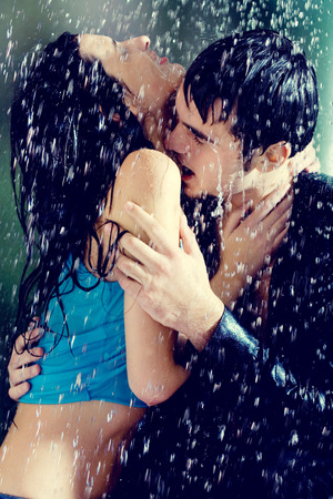Young couple hugging and kissing under a rain, in passion Banque d'images