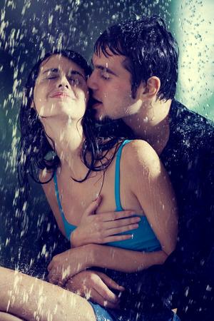 nudo maschile: Coppia giovane abbracciare e baciare sotto una pioggia, nella passione