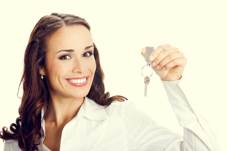 agents: Young happy smiling business woman or real estate agent showing keys from new house