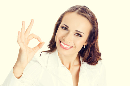 ok hand: Happy smiling young business woman with okay gesture