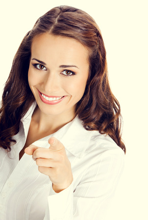 woman pointing: Portrait of young happy smiling business woman pointing finger at viewer