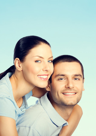 amorous: Cheerful young smiling amorous attractive couple, against blue sky background, with copyspace Stock Photo