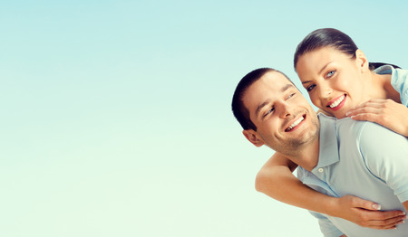 inlove: Cheerful young smiling amorous attractive couple, against blue sky background, with copyspace Stock Photo
