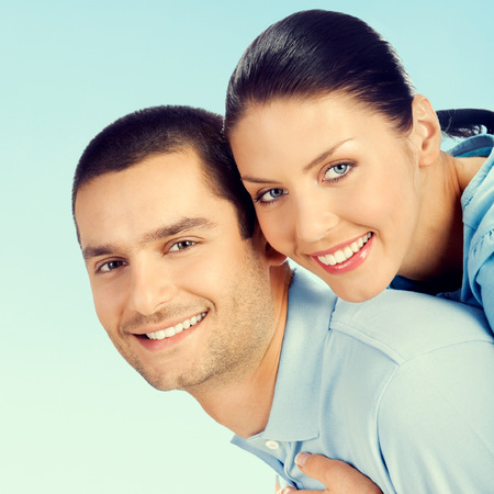 amorous: Cheerful young smiling amorous attractive couple, against blue sky background Stock Photo