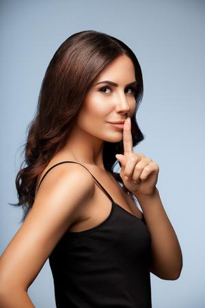 silencio: retrato de la hermosa mujer joven con el dedo en los labios, sobre fondo gris