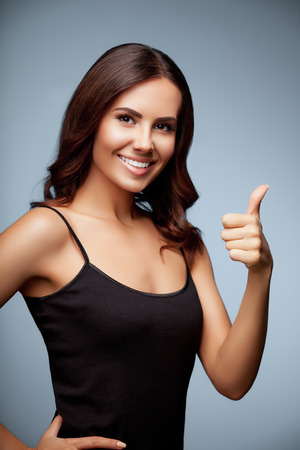 Portrait of beautiful cheerful smiling young woman showing thumb up hand sign gesture, over grey background Standard-Bild