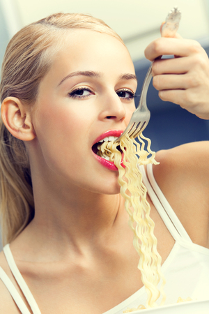 spaghetti: Happy smiling young blond lovely woman eating spaghetti indoors Stock Photo