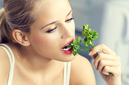 Young lovely woman eating coriander at domestic kitchen