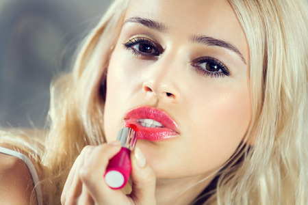 applying: Portrait of young lovely woman applying lipstick at home Stock Photo