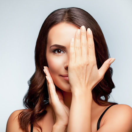 close eye: smiling young woman, with eye, clossed by hand, covering part of her face, over bright grey background, square composition Stock Photo