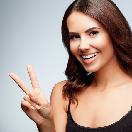 2 persons only: Beautiful young woman in black tank top clothing, showing two fingers or victory gesture, on bright grey background, square composition