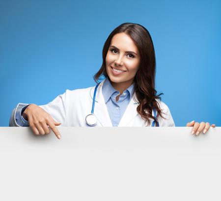 letreros: Retrato de feliz médico femenino joven sonriente que muestra señal en blanco, sobre fondo azul Foto de archivo