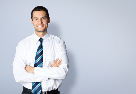 Portrait of happy smiling young businessman with crossed arms pose, posing at studio, against grey background, with blank copyspace area for slogan or text message