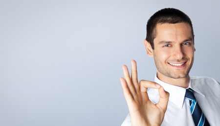 posing  agree: Happy smiling young businessman with okay gesture, posing at studio, against grey background, with blank copyspace area for slogan or text message Stock Photo