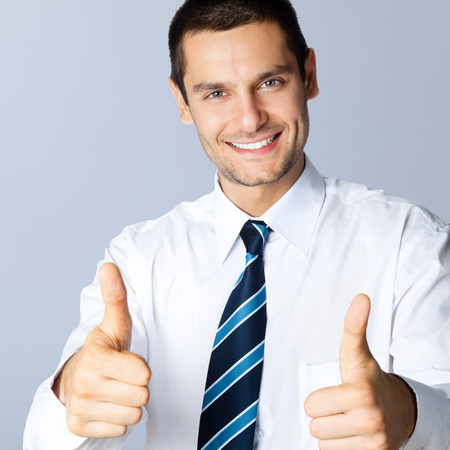 posing  agree: Portrait of happy smiling businessman with thumbs up gesture, posing at studio, against grey background Stock Photo