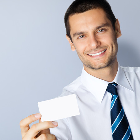 debet: Portrait of smiling businessman showing blank business or plastic credit card, with copyspace area for slogan or text message, posing at studio, against grey background