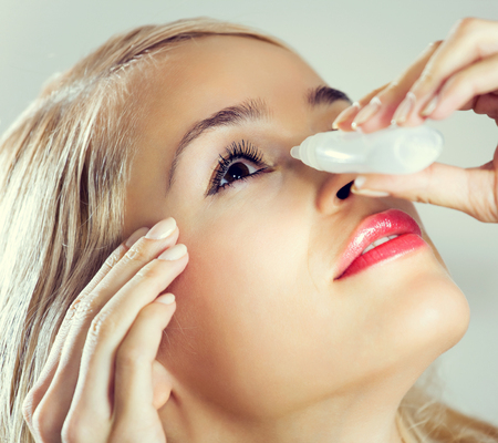 woman eye: Young lovely woman dripping eyes at home