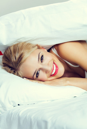 lazyness: Portrait of young happy smiling lovely woman waking up at bedroom