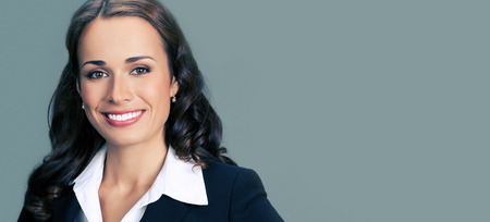 executive women: Portrait of cheerful smiling young businesswoman in black suit, with blank copyspace area for slogan or text