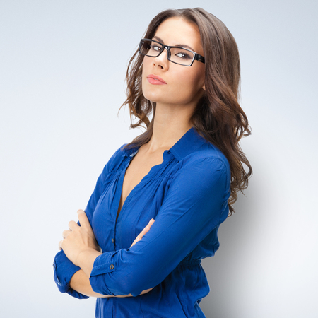 specs: Portrait of happy smiling young businesswoman in glasses, posing at studio Stock Photo