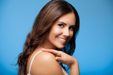 beautiful smile: Portrait of beautiful cheerful smiling young woman, on blue background Stock Photo