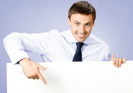 blank area: Portrait of happy smiling young business man showing blank signboard, over violet background