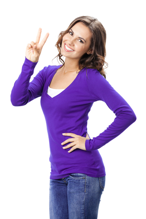 2 persons only: Happy smiling beautiful young woman showing two fingers or victory gesture, in violet casual clothing, isolated over white background