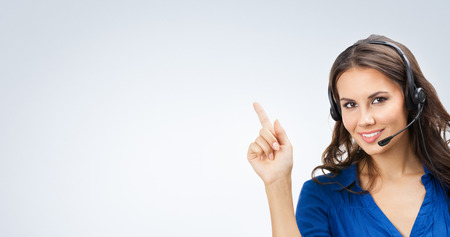 customer support: Portrait of happy smiling beautiful young support phone operator showing blank copyspace area for slogan or text, posing at studio