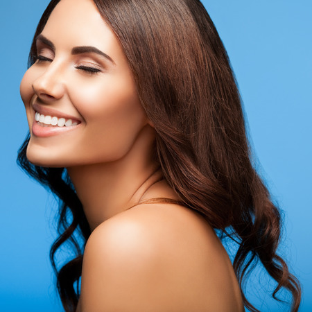 beautiful naked woman: portrait of beautiful smiling young woman with closed eyes, naked shoulders, on blue background