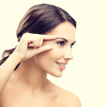 human eye: Portrait of beautiful young woman touching skin or applying cream