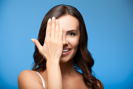 one eye: Concept photo of happy smiling young woman with one eye, closed by hand, covering part of her face, over blue background Stock Photo