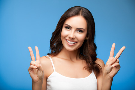 2 persons only: Portrait of beautiful young woman showing two fingers or victory gesture, on blue background Stock Photo