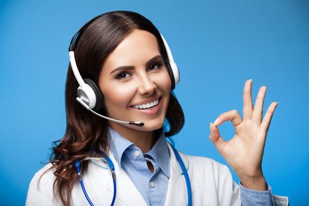 a ok: Portrait of smiling young female doctor in headset, showing okay gesture, on blue background