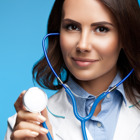 medicaid: Portrait of happy smiling female doctor with stethoscope in hand, on blue background