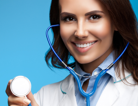 uniform attire: Portrait of happy smiling female doctor with stethoscope in hand, on blue background